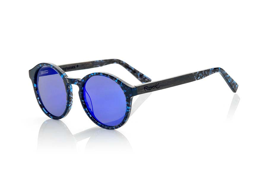 Wood eyewear of Ebony modelo ZORGE. ZORGE sunglasses of the MIXED PREMIUM series are manufactured with the front in acetate quality in color black with blue sparkles carey and sideburns in natural EBONY wood finished in Rod covered with acetate carey with blue flashes that can be adjusted if necessary. It's a model rounded suggestive shapes that are perfectly to people of both sexes and have been combined with grey lenses or blue REVO series. The quality of the materials and their perfect completion will surprise you. Front size: 140x51mm | Root Sunglasses®