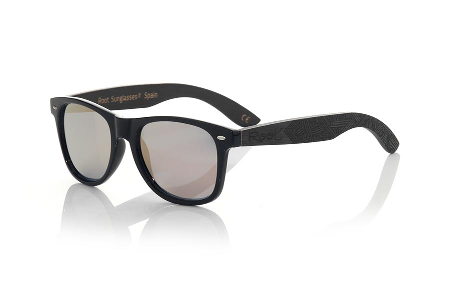 Wood eyewear of Bambú modelo SKA BLACK. The Ska black sunglasses are made with the black glossy PC front and the black tinted natural bamboo wood sideburns engraved with an ethnic pattern, combined with various colors of lenses that suit your style. Frontal measurement: 148x50mm | Root Sunglasses®