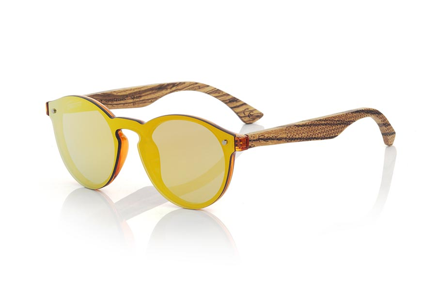 Wood eyewear of  modelo SUN ORANGE. SUN ORANGE sunglasses are made with transparent orange synthetic material front and sideburns in zebra wood engraved with an ethnic pattern, it's a female model rounded very current trend <b>PC not POLARIZED</b>flat lenses cover around the front. Front size: 136X49mm | Root Sunglasses®
