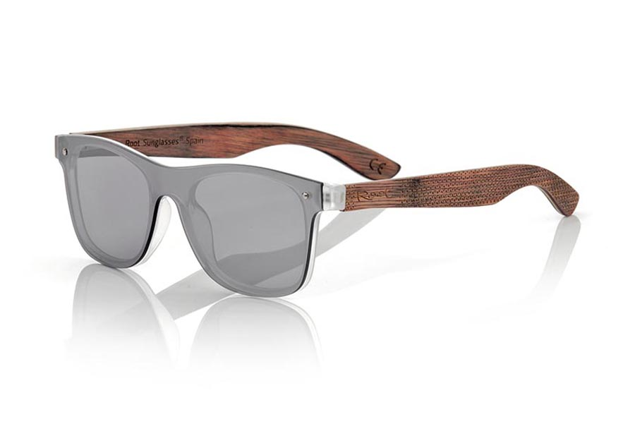 Wood eyewear of Skateboard modelo SKY SILVER. The SKY SILVER sunglasses are made with the front of transparent synthetic material and the laminated maple skateboard wood sideburns engraved with an ethnic pattern, it is a latest trend model, flat lenses <b> non-polarized PC </b> They cover the whole front. Frontal measurement: 152X48mm | Root Sunglasses®