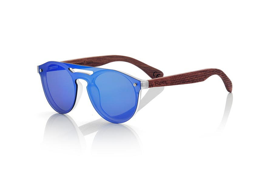 Wood eyewear of ROSEWOOD modelo SAMBA BLUE. The SAMBA BLUE sunglasses are made with the frontal of translucent synthetic material and the sideburns in ROSEWOOD wood engraved with an ethnic pattern, this is a very rounded female model of current trend the flat lenses <b> non-polarized PC </b> Cover the whole frontal.. Frontal measurement: 137X49mm | Root Sunglasses®