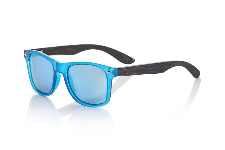Wood eyewear of Bamboo modelo SUN BLUE MX. SUN BLUE MX sunglasses are manufactured with the front panel transparent matte blue synthetic material and natural bamboo wood pins combined with four colors of lenses that allow you to adapt to your style. Front size: 145x48mm | Root Sunglasses®