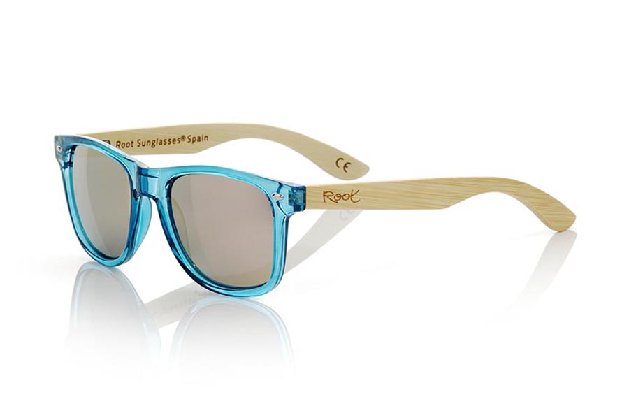 Wood eyewear of Bamboo modelo CANDY BLUE. The Candy Blue sunglasses are made with sinthetic front in blue transparent and sideburns in natural bamboo combined with four lens colors that will adapt perfectly to your taste and your modern style. Front Measure: 148x50mm | Root Sunglasses®