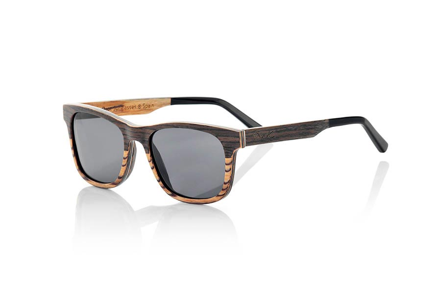 Wood eyewear of Black Walnut modelo NAMIB. NAMIB sunglasses are made from thin sheets of black walnut combined with Zebrano maera. The front image is a combination of black walnut on top and Zebrano wood at the bottom of it, the interior is wood Zebrano and incorporate a thin aluminum foil between the wooden slats on the front plus a blue colored sheet. The goggle is an angled SANDY model peaks marked at the sides of a smaller size, it is suitable for thin and sharp faces and the rods are finished in ethyl quality allowing its adjustment if necessary. The SANDY are ultra thin with only 4.2mm thick ultra light only 17gr and aluminum reinforcement brings a plus endurance plus a metallic touch in very elegant side. You'll be amazed the beauty of the combination of two woods in front lightness and finesse. NAMIB sunglasses include a practical folding case that keeps your glasses safe when they are  inside and takes up very little space when folded. Front Measure: 140x46mm | Root Sunglasses®