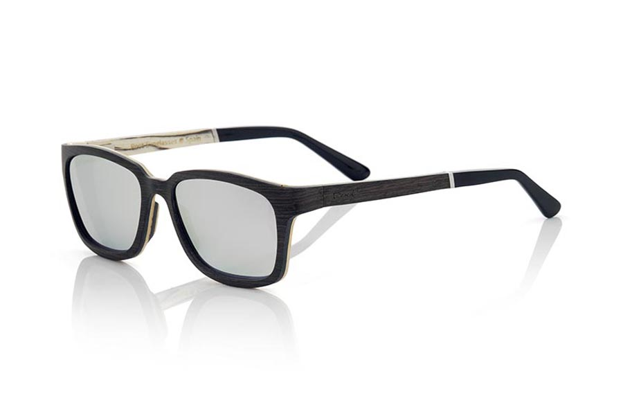 Wood eyewear of Mpingo modelo MADEIRA. The MADEIRA sunglasses are made of ebony wood and white wood, it is a laminated model of suggestive shapes and modern line where the hinge of the sideburns is presented in advance in the same and the laminated wood forms an angle of 90 º. The front of the MADEIRA is made of laminated wood of Mpingo on the outside and wood white wood inside, the sideburns are made with the same laminated scheme that the mount and end in acetate with rod that allows to be adjusted if necessary. You will be surprised by the combination of wood, its meticulous completion, its suggestive shape. Frontal measurement: 138x45mm | Root Sunglasses®