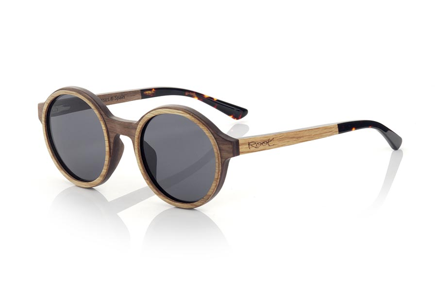 Wood eyewear of Walnut modelo NILIA. The NILIA sunglasses are manufactured in a combination of two woods, black walnut in frame and oak in the outer ring of the frame and temples. The latter are finished in hawksbill acetate with an internal rod, which allows it to be adjusted if necessary. It is a rounded model with its own personality with a very careful finish. Front measurement: 140x50mm | Root Sunglasses®